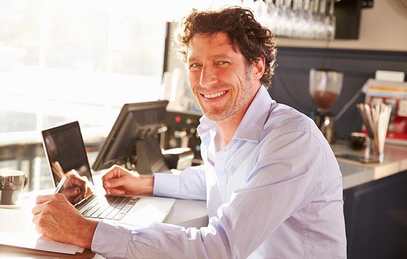 happy restaurant owner using apple laptop