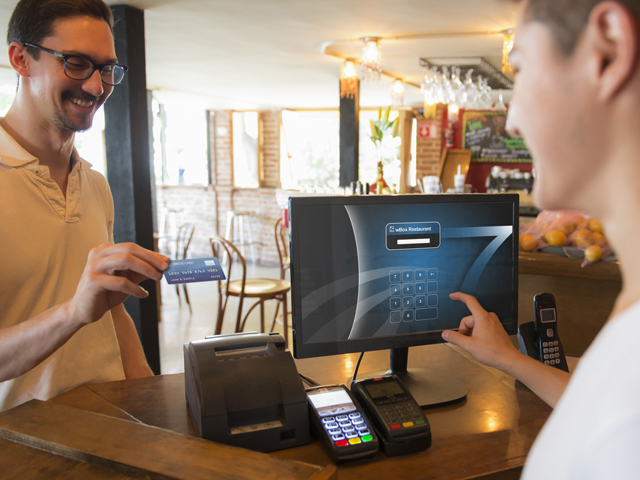 smiling man checking out at restaurant with credit card