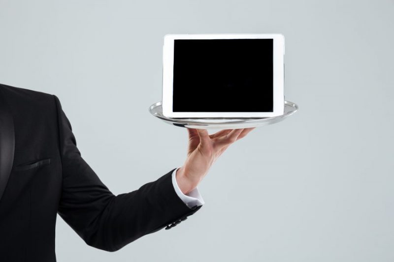 an ipad tablet point of sale being held on a silver tray by a male waiter in a black suit to show how great iPad POS software is for restaurants
