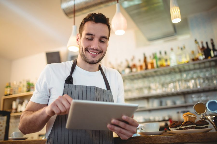 Happy male barista using digital tablet at cafe