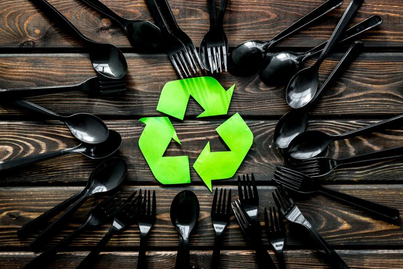 recycling and eco concept with plastic spoons and forks frame on wooden background top view