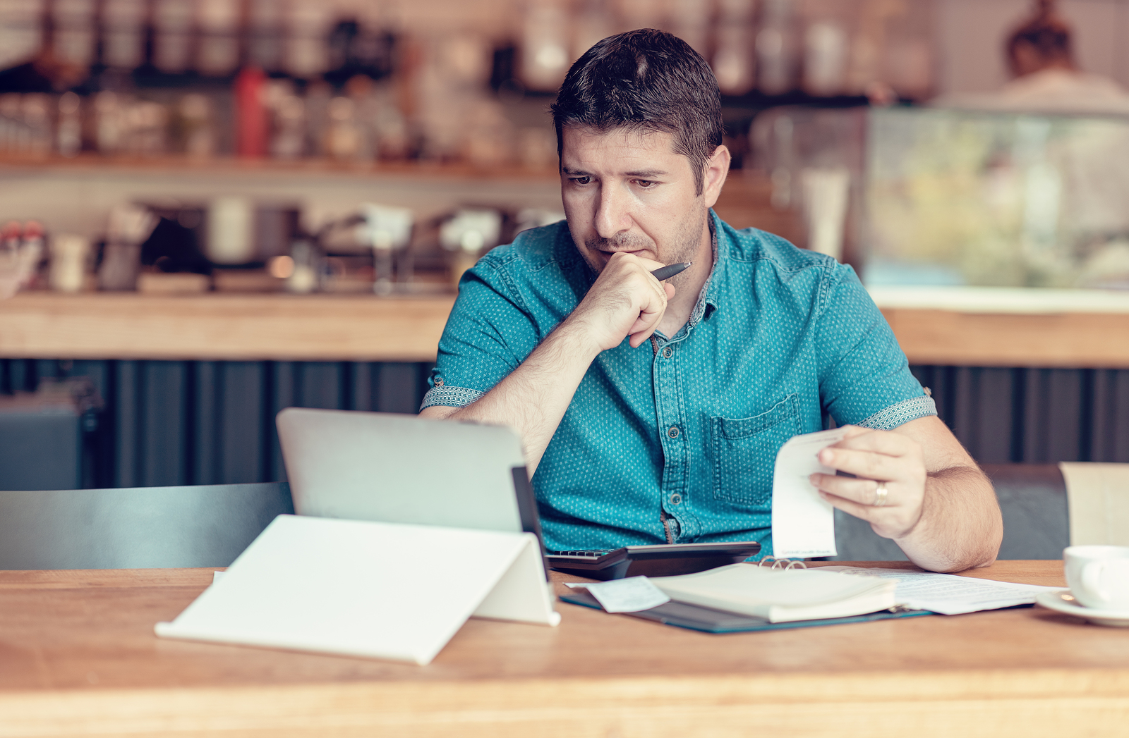 restaurant owner or manager looking through his reports on a tablet to find if there are ways to boost restaurant profits